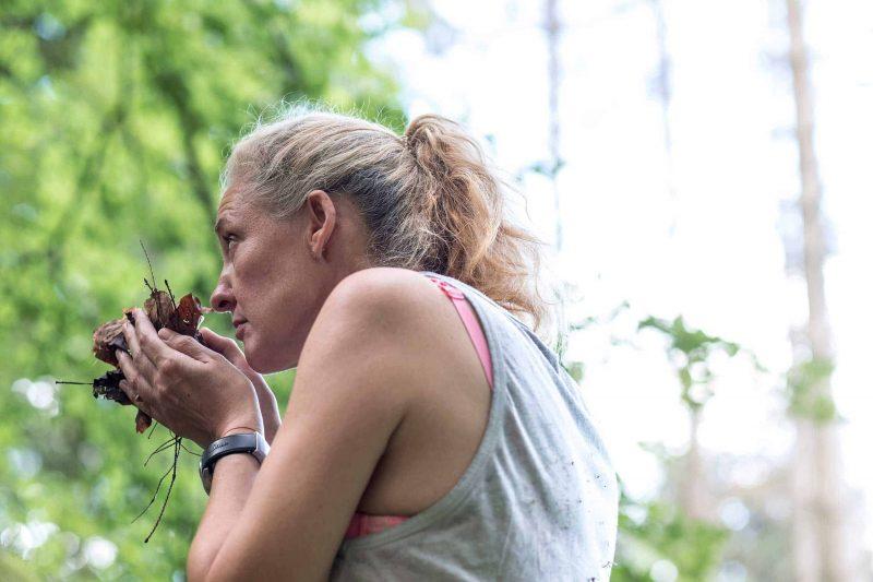 Eine junge Frau riecht beim Waldbaden an einer Hand voll trockener Blätter um deren Duft aufzunehmen.