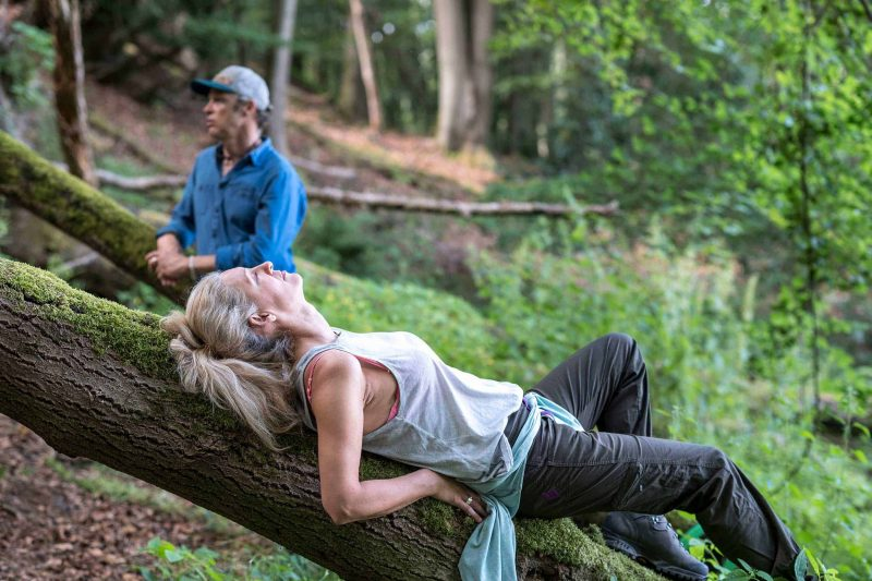 Eine Frau mit geschlossenen Augen liegt entspannt auf einem Baumstumpf. Im Hintergrund sieht man Waldbademeister Tom Haas mit einem blauen Hemd und blauer Kappe.