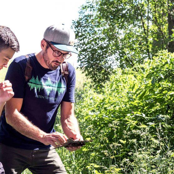 Ein Mann erklärt einem Jungen im Wald verschiedene Formen von Blättern eines Baumes.