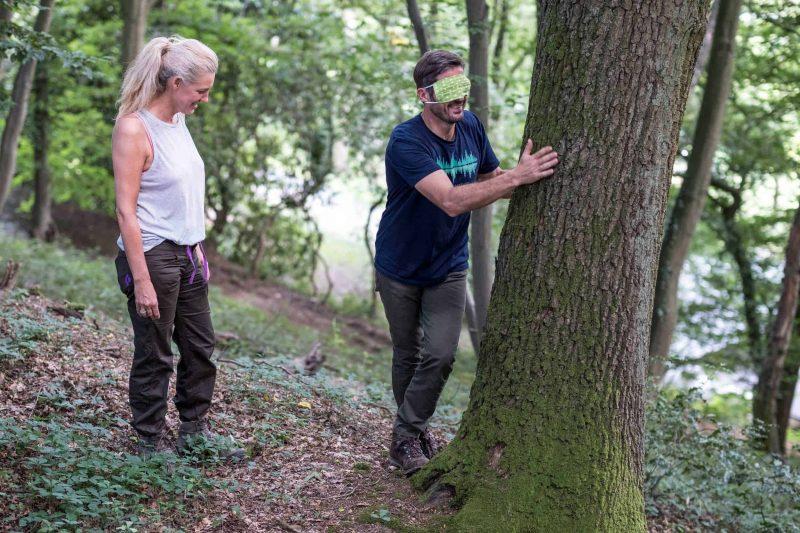 Ein Mann mit einer Augenbinde tastet einen Baum ab und eine Frau schaut ihm dabei zu. Waldbaden und Naturerlebnisse mit RobinWoods.