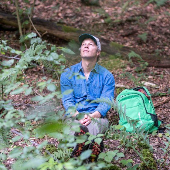 Seminarleiter Tom Haass genießt das Waldbaden und sitzt auf dem mit Laub bedeckten Waldboden.
