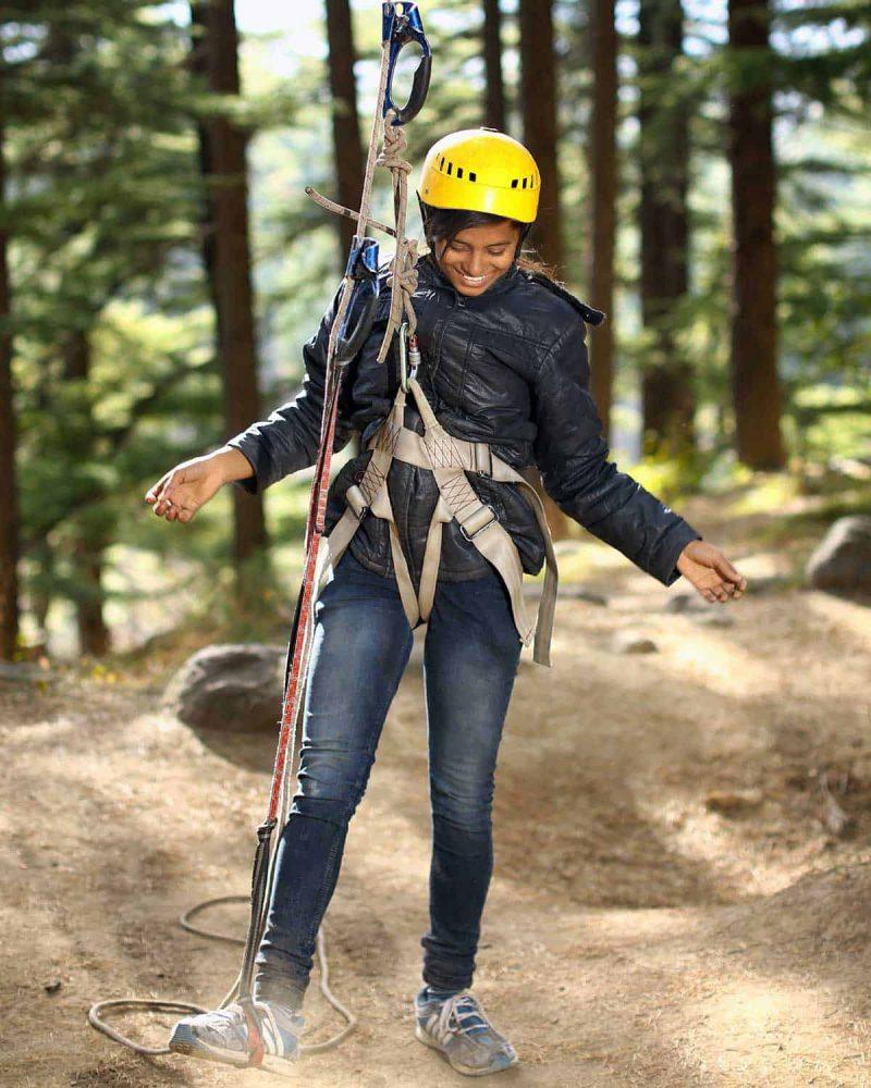 Ein Mädchen mit gelbem Helm hat ein Klettergeschirr für das Klettern in Bäumen angelegt. Baumklettern für Anfänger mit RobinWoods.