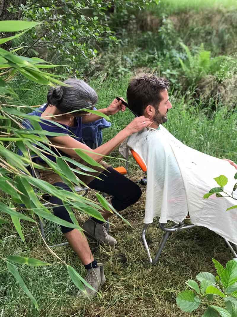 Eine Frau schneidet einem Mann im Wald die Haare. Der Open Hair Cut von Robinwoods.