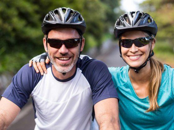 Ein Mann und eine Frau mit Helm und Sonnenbrille auf einer E-Bike Moutainbiketour mit Robinwoods Naturerlebnisse. Beide lächeln glücklich in die Kamera.
