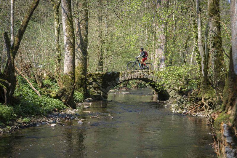 Radfahrer auf einer alten Bogenbrücke, die im Wal über einen kleinen Fluß führt.