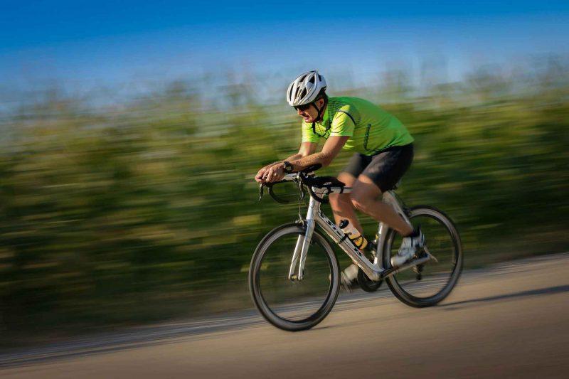 Ein Rennradfahrer in einem hellgrünen Trikot bei einer schnellen Abfahrt. Mit dem Rennrad durch den Westerwald.