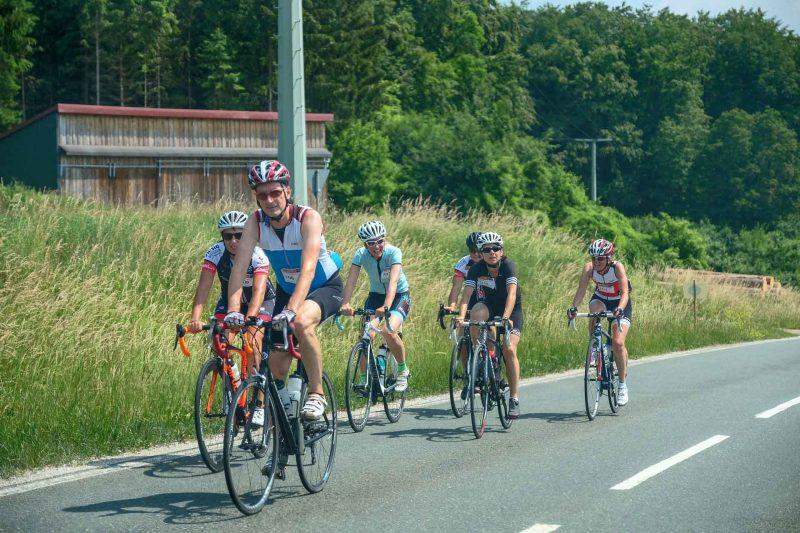 Eine Gruppe Rennradfahrer auf einer Fahrradtour auf einer Landstraße im Westerwald.