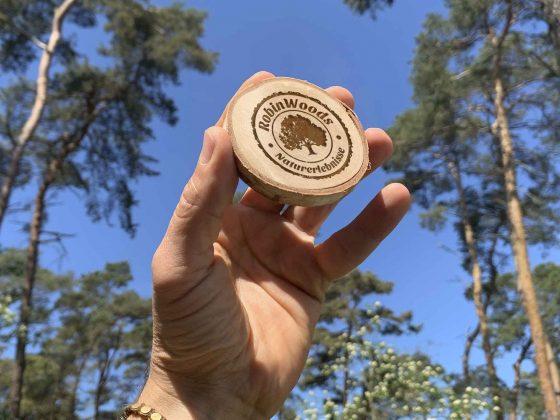 Eine Gutschein aus Holz wird von einer Hand in die Höhe gehalten. Die Holzscheibe mit dem RobinWoods Logo ist ein Gutschein für Walderlebnisse.