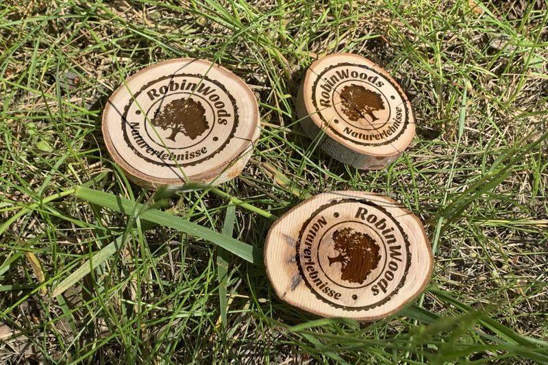 Holzscheiben mit dem RobinWoods Logo als Gutschein für Walderlebnisse.